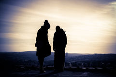 Silhouette of young couple  at sunset. Silhouette of young couple on the rooftop at sunset Royalty Free Stock Photography