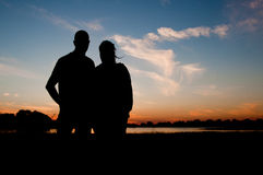 Silhouette of a young couple at sunset Stock Image