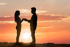 Silhouette of young couple at sunset Stock Photo