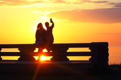 Silhouette young couple at sunset by the sea. Selfie stock image