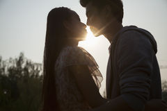 Silhouette of young couple very close to each other, sunbeam and lens flare Stock Image