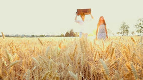 Silhouette of young couple walking across a wheat field. Man and woman in love at sunset light in a middle of nature with luggage / slow-mo / steady-cam stock footage