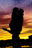Silhouette of a Young Couple by the water. A silhouette of a young couple sharing a kiss by the water at sunset royalty free stock photography