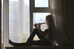Silhouette of young cute teen girl playing on flute sitting on windowsill at home. Youth hobby and leisure concept Stock Photo