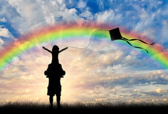 Silhouette of young dad with child and kite rainbow. Young dad holding a child on his shoulders on a rainbow background, and they launch a kite. Concept family Royalty Free Stock Image