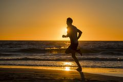 Silhouette young dynamic athlete runner man with fit strong body training on Summer sunset beach running barefoot in sport healthy. Silhouette of young dynamic royalty free stock image