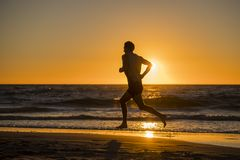 Silhouette young dynamic athlete runner man with fit strong body training on Summer sunset beach running barefoot in sport healthy stock photography