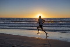 Silhouette young dynamic athlete runner man with fit strong body training on Summer sunset beach running barefoot in sport healthy royalty free stock image