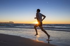 Silhouette young dynamic athlete runner man with fit strong body training on Summer sunset beach running barefoot in sport healthy royalty free stock photos