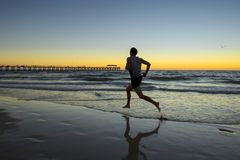 Silhouette young dynamic athlete runner man with fit strong body training on Summer sunset beach running barefoot in sport healthy stock photo