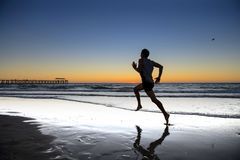 Silhouette young dynamic athlete runner man with fit strong body training on Summer sunset beach running barefoot in sport healthy stock photos