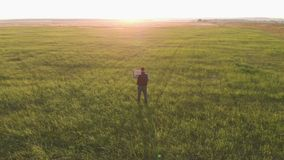 Silhouette young farmer going on the field at sunset with wooden box with fresh vegetables. Healthy eating, autumn stock footage