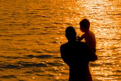Silhouette of a young father entering the sea holding a little son in his arms against the background of a sunset stock image