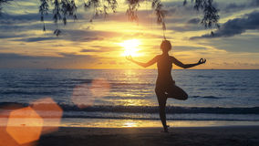 Silhouette young female practicing yoga on beach at sunset. Morning. Royalty Free Stock Images