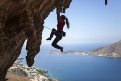 Silhouette of a young female rock climber on a cliff. stock photo