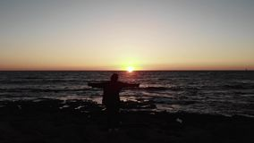 Silhouette of young female woman standing on the rocky beach with hands widespread to sides on sunset over the wavy sea with sun r. Oad. Aerial drone view stock video footage