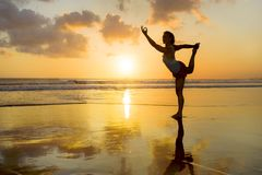Silhouette of young fit and attractive sport woman in beach sunset yoga practice workout standing on wet sun in front of sea in me. Ditation and relaxation Stock Photo