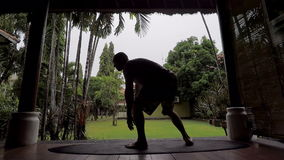 Silhouette of young fit man having training of trunk curl on surfboard on terrace of tropical bamboo house. Athlete. Trainee is lying down on the ground and stock footage