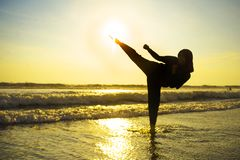 Silhouette of young fit Muslim woman covered in Islam hijab head scarf training martial arts karate kick attack and fitness. Silhouette of young fit and royalty free stock photo