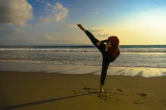 Silhouette of young fit Muslim woman covered in Islam hijab head scarf training martial arts karate kick attack and fitness. Silhouette of young fit and stock photo