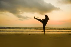 Silhouette of young fit Muslim woman covered in Islam hijab head scarf training martial arts karate kick attack and fitness. Silhouette of young fit and stock photos