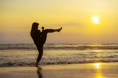 Silhouette of young fit Muslim woman covered in Islam hijab head scarf training martial arts karate kick attack and fitness. Silhouette of young fit and royalty free stock images