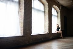 Silhouette of a young, flexible well shaped ballerina sitting on the huge window. Concept of loneliness and sadness