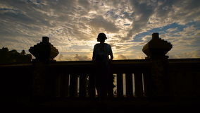 Silhouette of a young girl with a backpack goes to the fence and looking away before sunset. backlight. Silhouette of a young girl and relaxed freely dressed stock footage