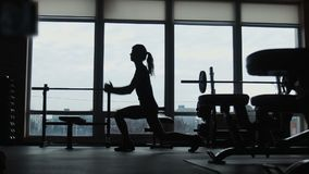 The silhouette of the young girl, does squats jumps in a gym