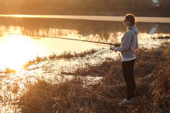 Silhouette of a young girl fishing at sunset near the lake Stock Photo