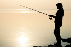 Silhouette of a young girl fishing at sunset Stock Photos