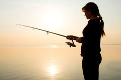 Silhouette of a young girl fishing at sunset near Stock Photos