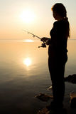 Silhouette of a young girl fishing at sunset near the sea Stock Photo