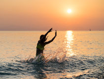 Silhouette of young girl jumping in sea Stock Images