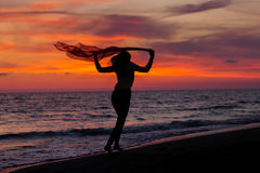 Silhouette of young girl, jumping with silk cloth against of sea sunset Royalty Free Stock Images