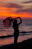 Silhouette of young girl, jumping with silk cloth against of sea sunset stock photos