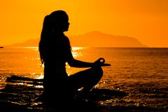 Silhouette of young girl meditating on the sea. Silhouette of young girl meditating at the morning sunrise on the coast of Red sea in yoga pose Royalty Free Stock Photos