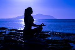 Silhouette of young girl meditating on the sea. Silhouette of young girl meditating at the morning sunrise on the coast of Red sea in yoga pose Stock Image