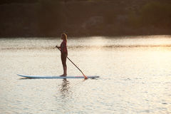 Silhouette of young girl paddle boarding at sunset02 Royalty Free Stock Photography
