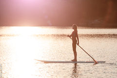 Silhouette of young girl paddle boarding at sunset01. SUP Stand up paddle board woman paddleboarding royalty free stock images