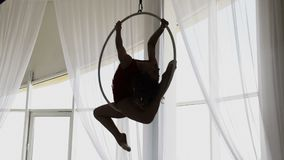 Silhouette young girl performs the acrobatic elements in the air ring.  stock video