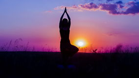 Silhouette of a Young Girl Practicing Yoga At