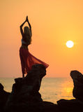 A silhouette of a young girl on rock at sunset 2. A silhouette of a young girl doing yoga at sunrise or sunset on rock wearing a wrap stock photos