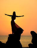 A silhouette of a young girl on rock at sunset 3. A silhouette of a young girl doing yoga at sunrise or sunset on rock wearing a wrap stock image