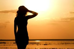 Silhouette of a young girl on the sea in a hat Stock Photography
