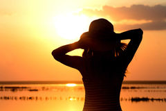 Silhouette of a young girl on the sea in a hat Royalty Free Stock Photo