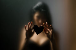 Silhouette of young girl sexual. Silhouette of young girl for sexual opaque glass with paper heart in hands Royalty Free Stock Image