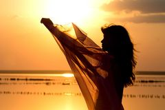 Silhouette of a young girl with a shawl Stock Photos
