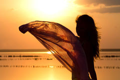 Silhouette of a young girl with a shawl Royalty Free Stock Image