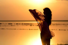 Silhouette of a young girl with a shawl. On the sea Royalty Free Stock Photography